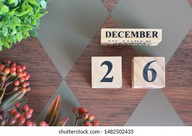 December 26. Date of December month. Number Cube with a flower and leaves on Diamond wood table for the background