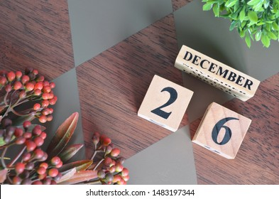 December 26. Date of December month. Number Cube with a flower leaves and bush on Diamond wood table for the background