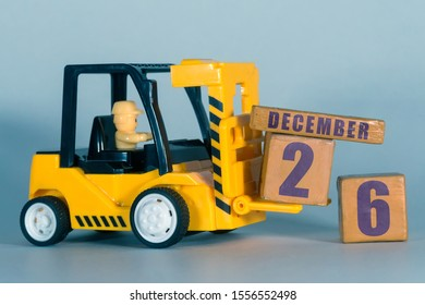 december 26th. Day 26 of month,  Construction or warehouse calendar. Yellow toy forklift load wood cubes with date. Work planning and time management. winter month, day of the year concept.