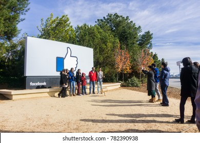 December 27, 2017 Menlo Park / CA / USA - A group of friends posing in front of the Facebook Like Button sign located at the entrance to the company's main headquarters located in Silicon Valley