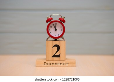 December 2nd set on wooden calendar and red alarm clock with blue background. Clock face showing five minutes to midnight