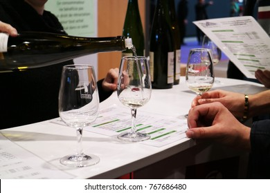 December 3, 2017 :Porte de Versailles, Paris, France - Hand of a seller pouring a white wine in a glass serving to the tasters in the expo at French vigneron independant winemaker fair 2017