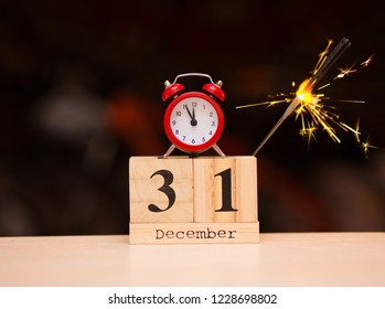 December 31st set on wooden calendar with red alarm clock on dark blurred background. Clock face showing five minutes to midnight