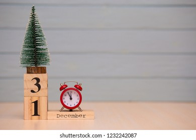 December 31st set on wooden calendar with new year tree and red alarm clock on blue background. Clock show five minutes to midnight