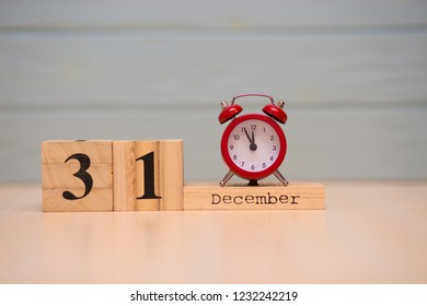 December 31st set on wooden calendar and red alarm clock with blue background. Clock show five minutes to midnight