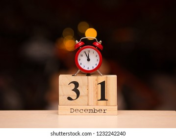 December 31st set on wooden calendar with red alarm clock on dark blurred background. Clock show five minutes to midnight