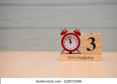 December 3rd set on wooden calendar and red alarm clock with blue background. Clock face showing five minutes to midnight