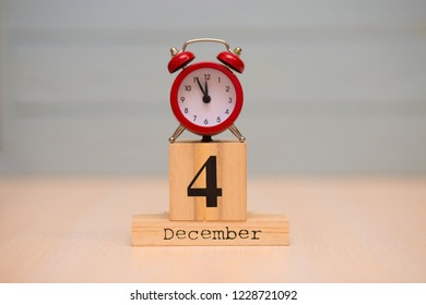December 4th set on wooden calendar and red alarm clock with blue background. Clock face showing five minutes to midnight