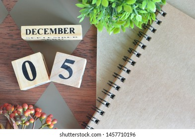 December 5. Date of December month. Number Cube with a flower and notebook on Diamond wood table for the background.