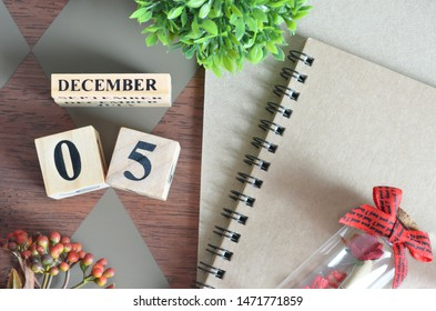 December 5. Date of December month. Number Cube with a flower, Rose bottle and notebook on Diamond wood table for the background.