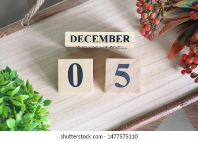 December 5. Date of December month. Number Cube with a flower and Sign wood on Diamond wood table for the background.