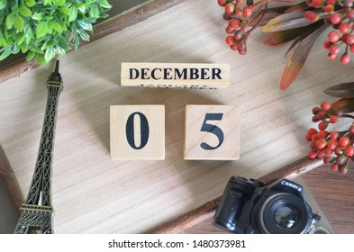 December 5. Date of December month. Number Cube with a flower camera and Sign wood on Diamond wood table for the background.