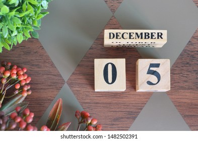 December 5. Date of December month. Number Cube with a flower and leaves on Diamond wood table for the background