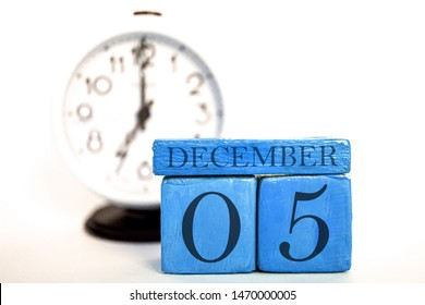 december 5th. Day 5 of month, handmade wood cube calendar and alarm clock on  blue color. winter month, day of the year concept.