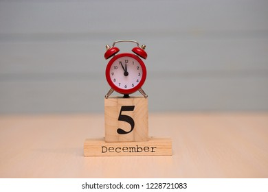 December 5th set on wooden calendar and red alarm clock with blue background. Clock showing five minutes to midnight