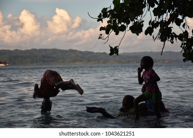 December 6, 2017 - Kampoeng Bni Wisata, Arborek, Raja Ampat - Kids enjoying themselves while jumping into the sea again and again just before Sun set