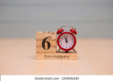 December 6th set on wooden calendar and red alarm clock with blue background. Clock showing five minutes to midnight