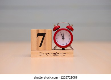 December 7th set on wooden calendar and red alarm clock with blue background. Clock face showing five minutes to midnight