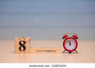 December 8th set on wooden calendar and red alarm clock with blue background. Clock face showing five minutes to midnight
