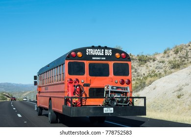 DECEMBER 9 2017 - TUSCON, AZ: A Struggle Bus drives down an Arizona highway with equipment carried on a trailer on a sunny day.