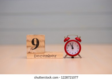 December 9th set on wooden calendar and red alarm clock with blue background. Clock face showing five minutes to midnight