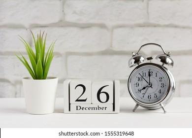 December, alarm clock and calendar on the table.December 26 on a wooden calendar next to the clock