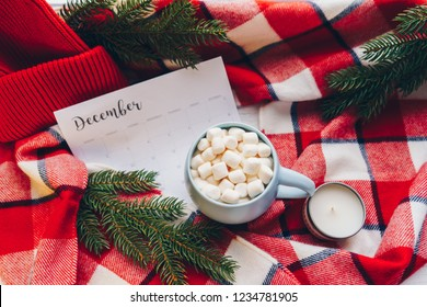 December Calendar with blank space. Christmas holiday mood concept. Cocoa mug with marshmellow and Christmas decoration on the red plaid background. Planning. Flat lay. Top view