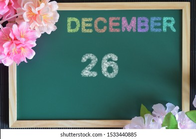 December month write with colorful chalk, flowers on the board, Date 26.