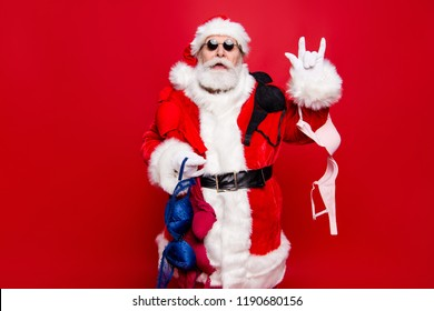 December noel winter wish Christmastime. Mature aged stylish trendy grandfather Santa spectacles tradition headwear costume white beard show rock n roll heavy metal sign isolated red background