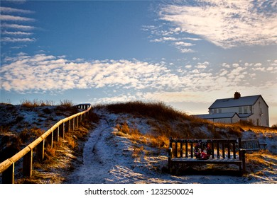 December snow fall on Rocky Island, Seaton Sluice in Northumberland. The low sun casting long shadows and a snow covered remembrance seat is a reminder of the poignancy of the Christmas season