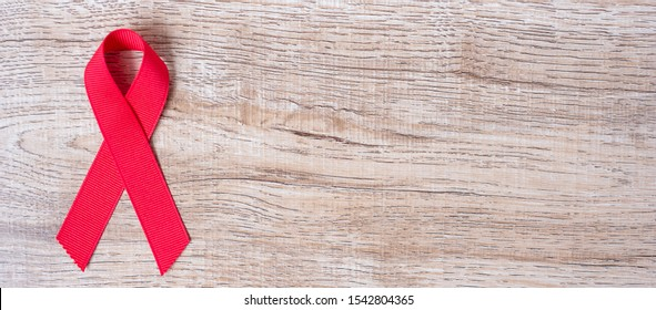 December World Aids Day Awareness month, Red Ribbon on wood background for supporting people living and illness. Healthcare and safe sex concept