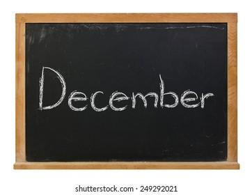 December written in white chalk on a black wood framed chalkboard isolated on white