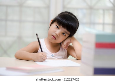Decent school child. holding her head with a hand and reading a book