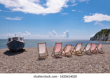 Dechairs and boaton shingle beach at Beer, Devon, United Kingdom