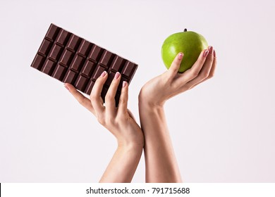 Deciding what to choose. Close up of sports woman hands with chocolate and apple isolated on white background. Hard choice between healthy and unhealthy food. Sweet temptation of fitness girl