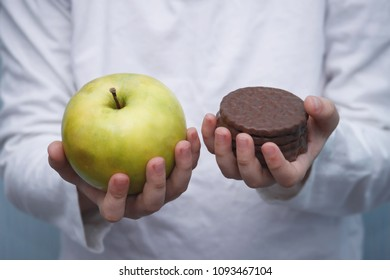 Deciding what to choose. Kid's  hands with chocolate cookie and green apple. Hard choice between healthy and unhealthy food.