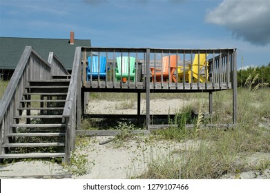 Deck at the beach with colorful array of Adirondack chairs for relaxing oceanfront.