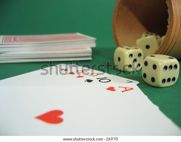 A deck of cards and a dice box with dice on green background.