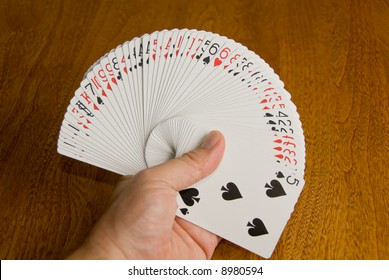 Deck of cards spread in a pressure fan in the left hand.