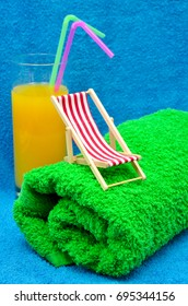 deck chair with green towel and cocktail close up photo