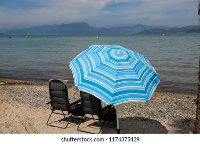 Deck chair and umbrella on Lake Garda