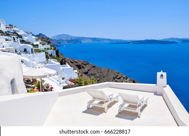 Deck chairs on terrace with spectacular view over volcanic caldera, Santorini Island, Greece