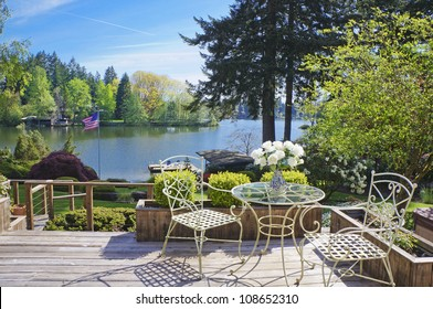 Deck with chairs and table with lake view and spring landscape.