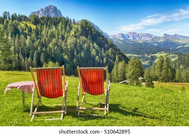 deck chairs and table on the lawn overlooking the mountains and the valley in summer