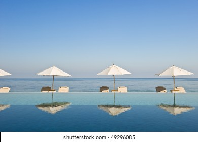 Deck chairs under sun umbrella between an infinity pool and the sea. Copy space provided on top.