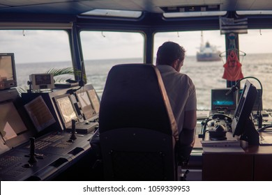 Deck navigation officer on the navigation bridge. He looks at radar screen. Watchkeeping, collision prevention at sea. COLREG