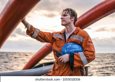 Deck Officer on deck of offshore vessel or ship , wearing PPE personal protective equipment. He holds VHF walkie-talkie radio in hands. Dream work at sea