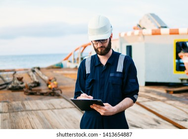 Deck Officer on deck of offshore vessel or ship , wearing PPE personal protective equipment. He fills checklist. Paperwork at sea