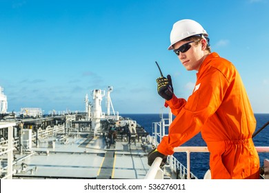 Deck officer using radio on the board of a tanker.