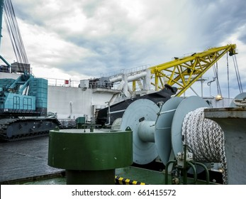The deck of the pipe-lay vessel. Cable winch and boom for pipes. The submersible on deck